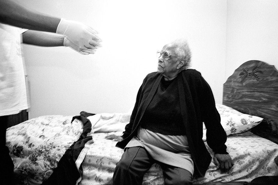 An elderly woman sits on her bed, while her caregiver reaches out to her.
