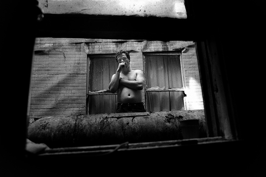 A shirtless man viewed through a window.