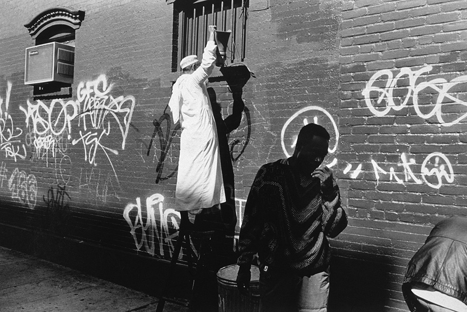 Two men in front of a graffitied wall.