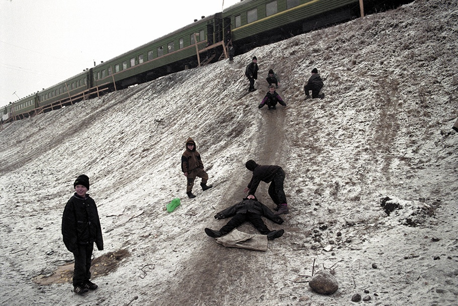 Children playing on a snowy hill with a train above.