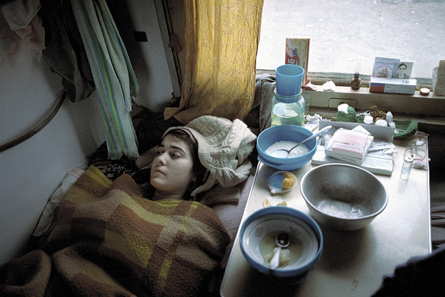 A woman reclining next to a table with food.