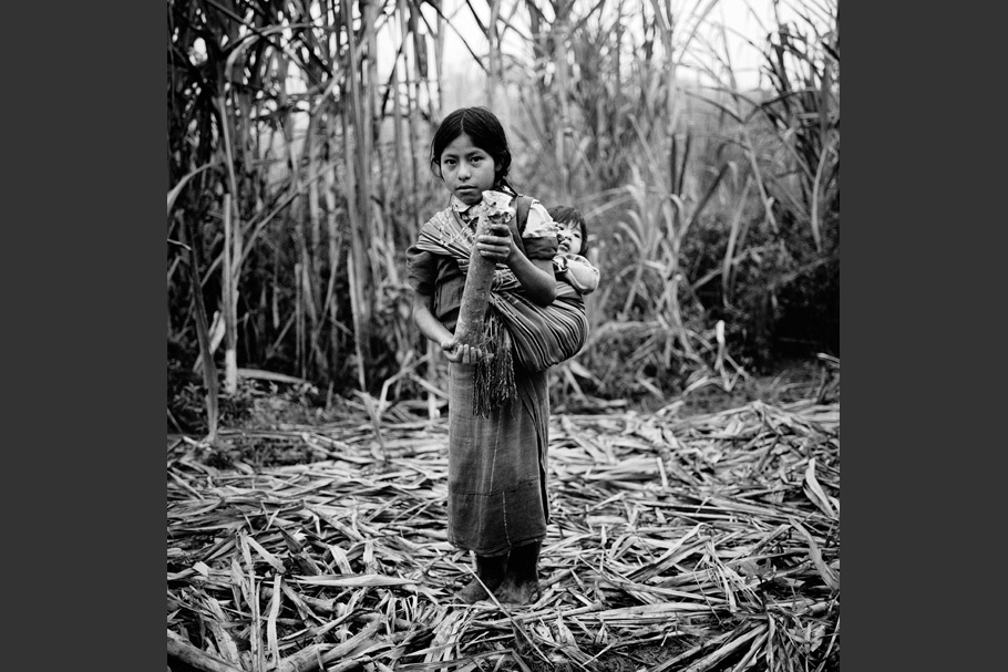 A girl with a baby on her back, holding a mortar shell.