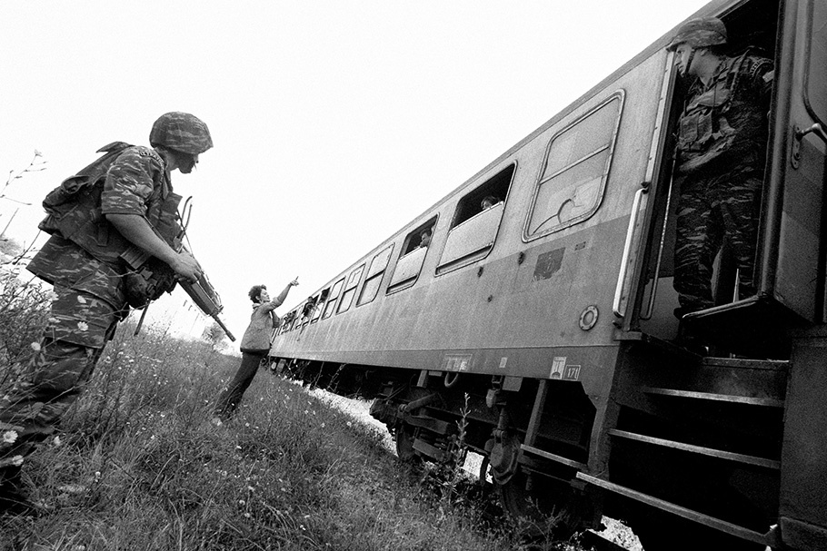 An armed soldier stands outside a train