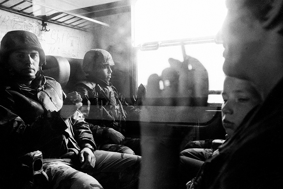 Soldiers sitting in a train compartment.