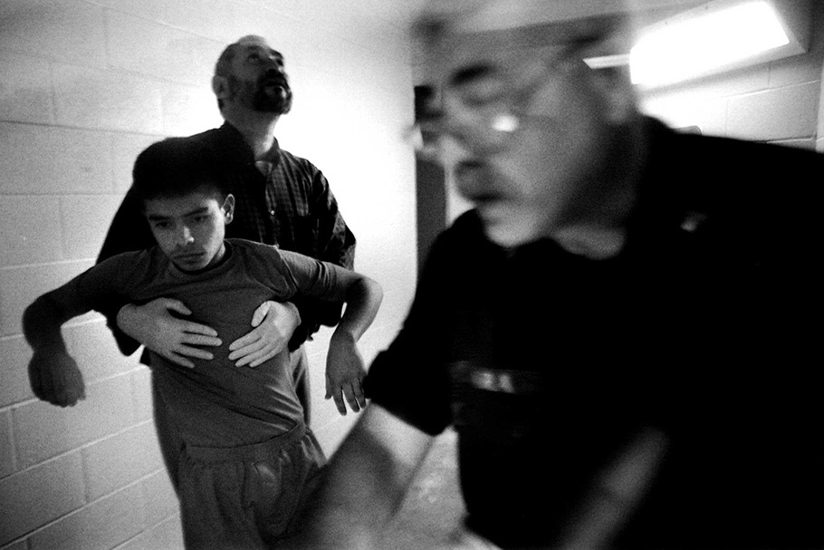 A boy is held up by an officer, with another in the foreground.