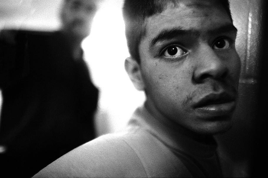 Close up of a boy with a blurred officer in the background.