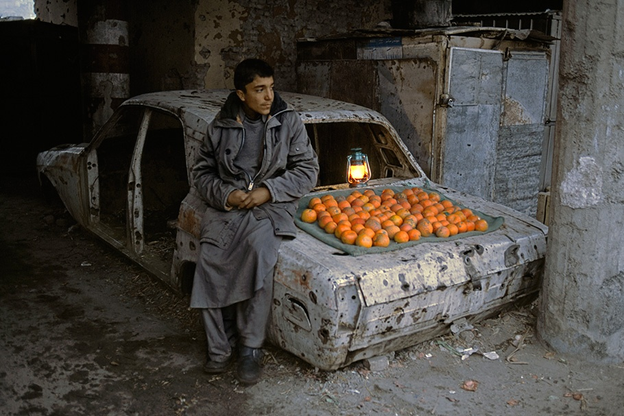 A vendor selling oranges from a car.