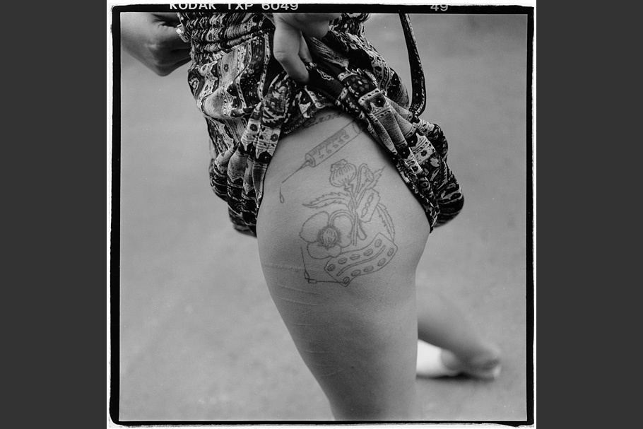 A woman showing her tattooed thigh.