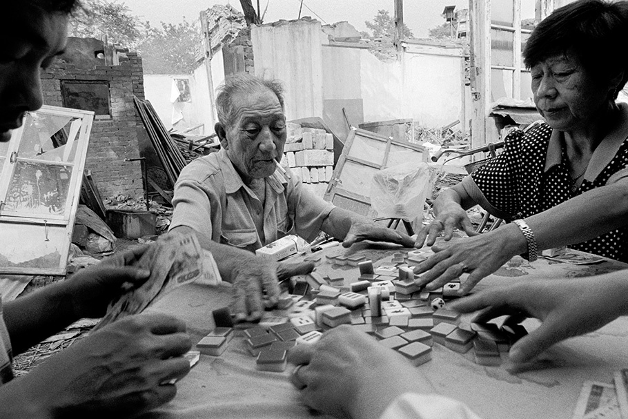 People playing mahjongg surrounded by rubble.
