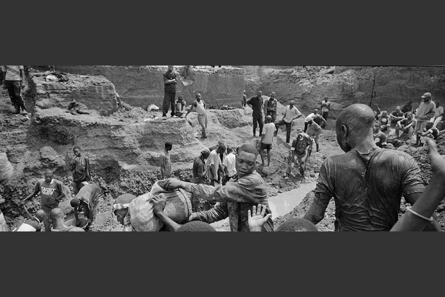 Workers carrying a sack out of a mine.