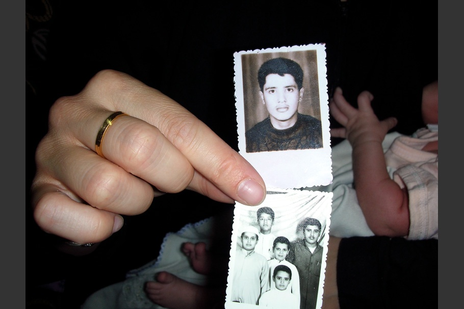 A hand holding two small photographs.
