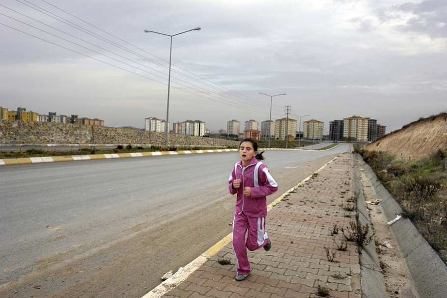Girl running in pink track suit.