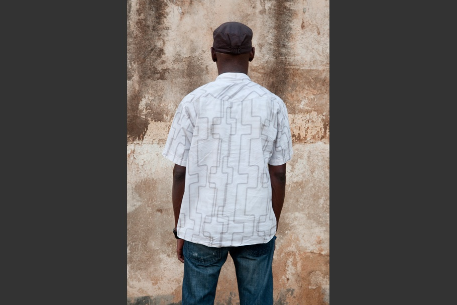 White vertical patterned short sleeved collared shirt, hat.