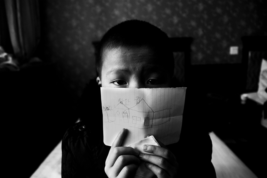 A young boy holds a piece of a paper in front of his face.