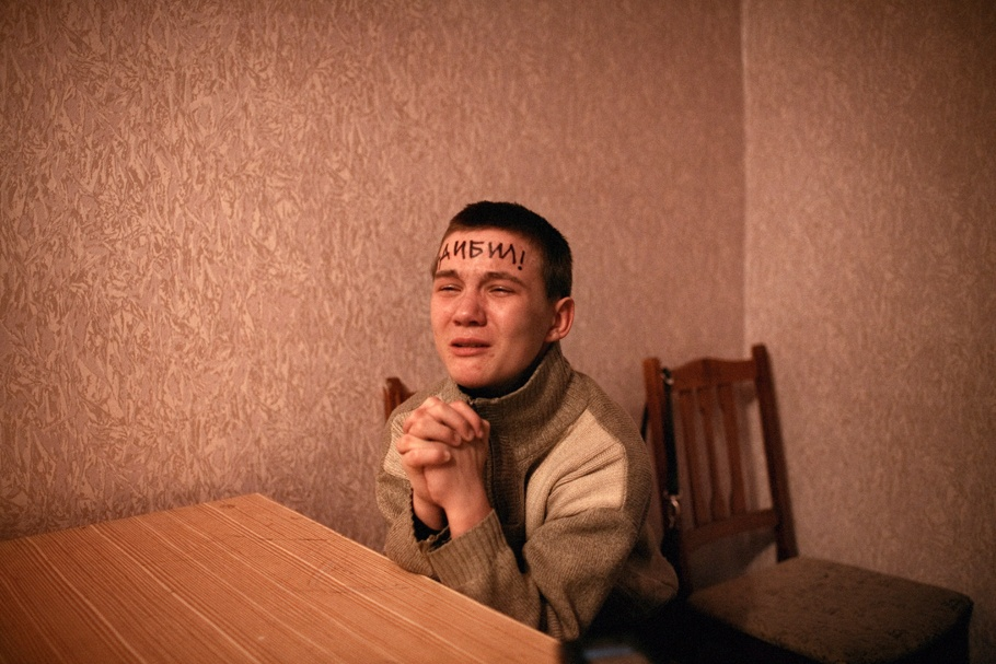 A young boy crying with clasped hands and words written on his forehead.