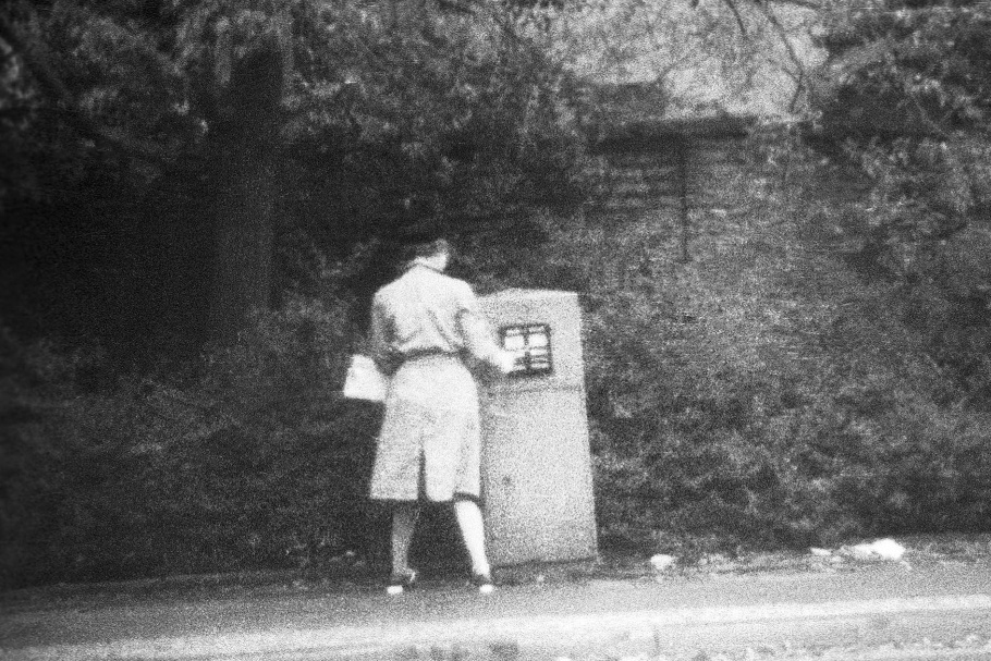 Woman with trench coat and black hat placing mail in mailbox