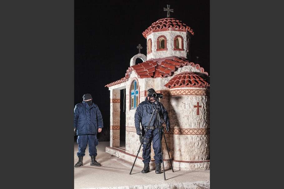 Two border patrol police stand in front of small chapel