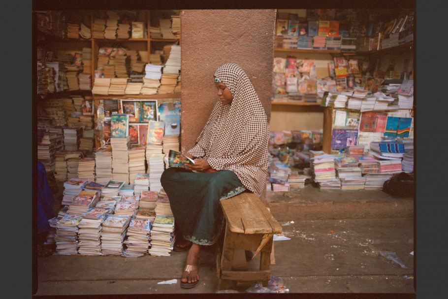 A Nigerian romance novelist reads a book outside a bookstall