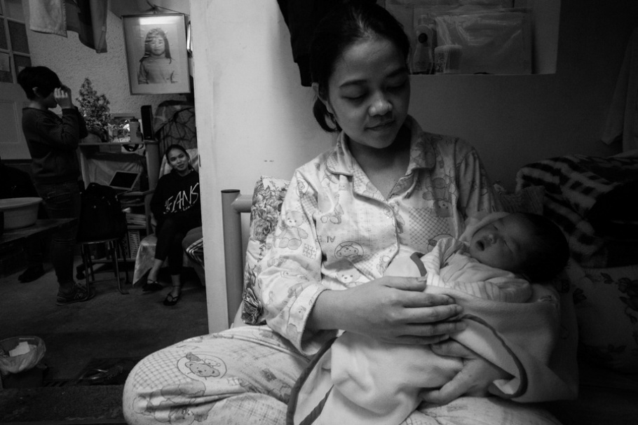 A woman holding a newborn baby.