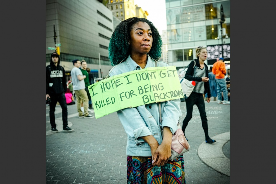 "A woman in the street with a sign that says, ""I hope I don't get killed for being black today."""