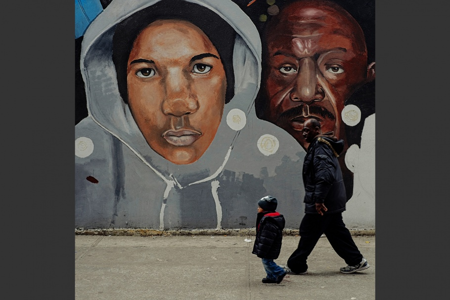A man and a boy walking in front a mural.