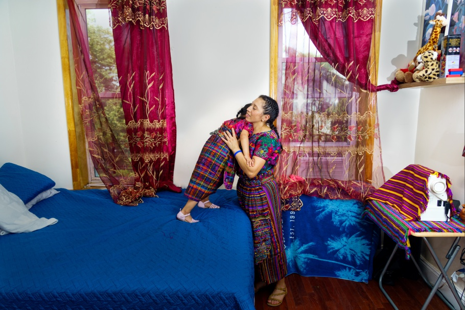 A woman hugging a child who is standing on a bed