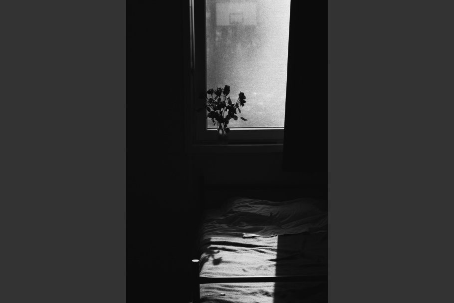 An empty bed with flowers on a windowsill