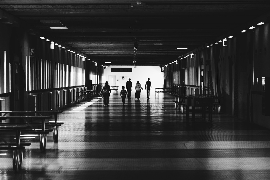 Adults and a child walk through an empty lunchroom
