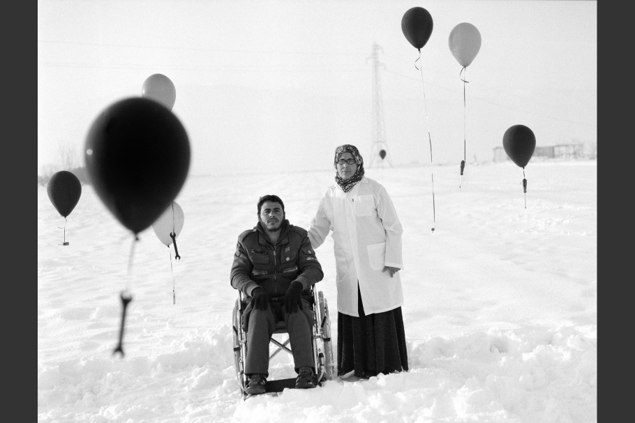A man in a wheelchair and a woman standing in the snow