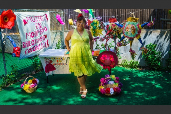 A woman standing in front of a table with piñatas nearby