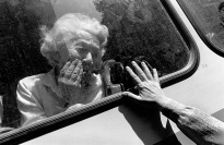An elderly woman viewed through a vehicle window.