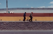 Two men walking along the border.