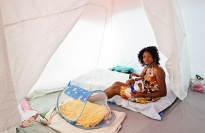 Woman sitting in a tent with baby.